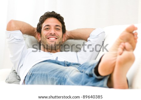 Smiling healthy young man relaxing on sofa and looking at camera - stock photo