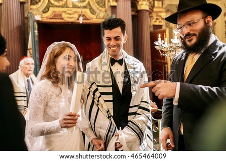 Smiling hebrew looks at a happy bride standing behind a groom