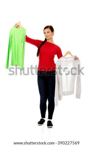 Smiling hesitant young woman holding two shirts - stock photo