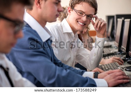 Smiling highschool student with glasses sitting in classroom - stock photo