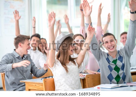 Smiling highschool students in classroom holding hands in the air - stock photo
