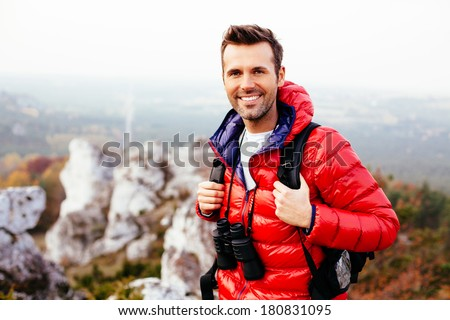 Smiling hiker on the trail looking at camera - stock photo