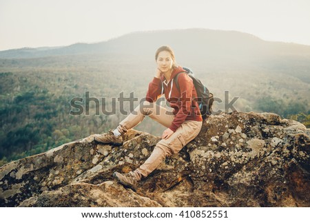 Smiling hiker young woman with backpack sitting on peak of rock on background of mountains and looking at camera in summer outdoor