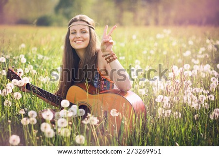 Smiling hippie woman giving peace sign. Freedom and harmony - stock photo