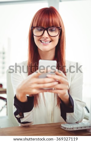 Smiling hipster businesswoman texting on her smartphone in office