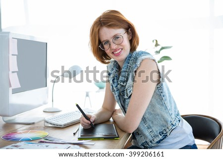 smiling hipster businesswoman writing on a digital drawing tablet in her office - stock photo