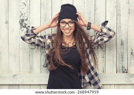 Smiling hipster girl in glasses and black beanie on the wooden background - stock photo