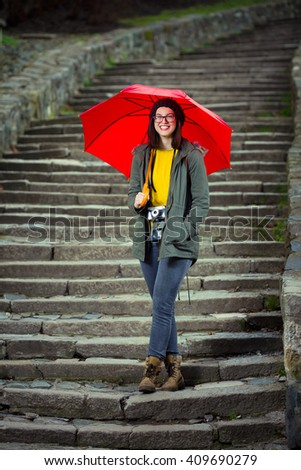 Smiling hipster girl is walking down the stairs of the fortress in an old town. She is holding a red umbrella and looking at camera. - stock photo