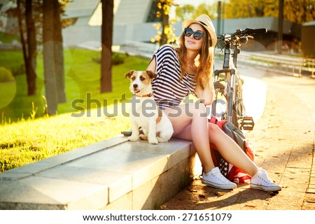 Smiling Hipster Girl with her Dog and Bike in the City. Toned and Filtered Photo with Bokeh and Copy Space. Urban Youth Lifestyle Concept. - stock photo