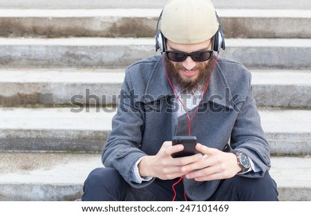 Smiling hipster guy listening to his favourit music. - stock photo