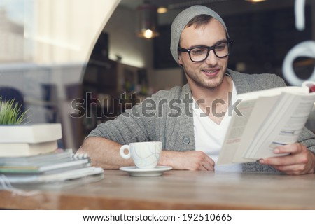 Smiling hipster man reading book at cafe  - stock photo