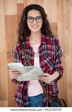 Smiling hipster with map on wooden background