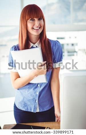 Smiling hipster woman holding document in her office