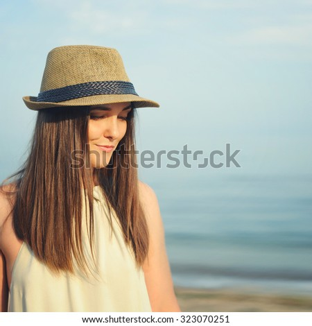 Smiling hipster woman outdoor portrait with long beautiful hairs and hat against sea landscape.