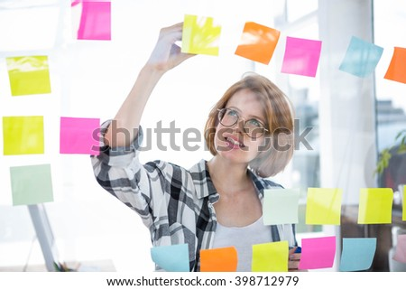 smiling hipster woman sticking notes on a notice board in the office - stock photo