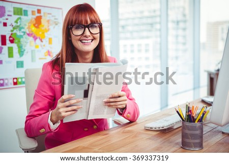 Smiling hipster woman with a book in office