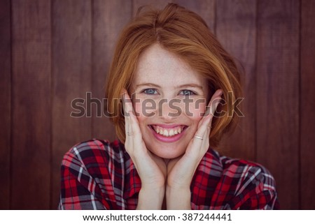 smiling hipster woman with her hands on her face against a wooden background - stock photo
