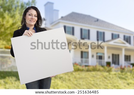 Smiling Hispanic Female Holding Blank Sign In Front of Beautiful House. - stock photo
