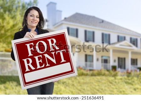 Smiling Hispanic Female Holding For Rent Sign In Front of Beautiful House. - stock photo