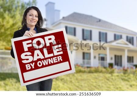 Smiling Hispanic Female Holding For Sale By Owner Sign In Front of Beautiful House. - stock photo