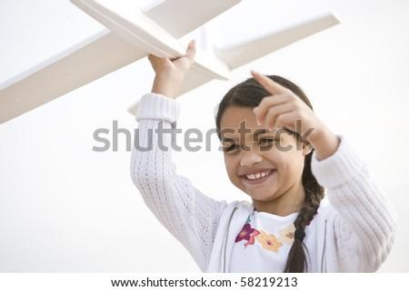 Smiling Hispanic girl playing with toy model plane - stock photo