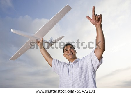 Smiling Hispanic man holding model airplane glider over head - stock photo