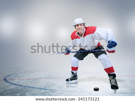 Smiling hockey player on ice - stock photo