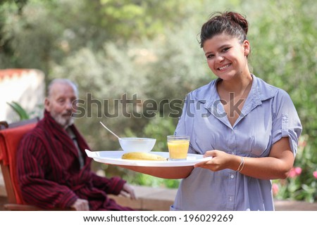 smiling home carer serving meal to elderly man - stock photo