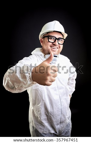 Smiling house painting equipped with protective suit and mask, helmet, white teeth, casual glasses, thumbs up. Black background.