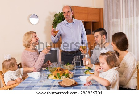 Smiling housefather says toast at the dinner table in front of his friendly family indoor