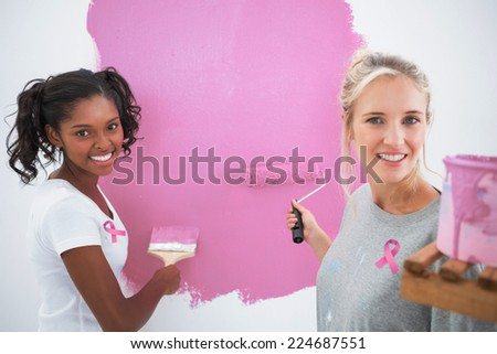 Smiling housemates painting wall pink against pink breast cancer awareness ribbon - stock photo