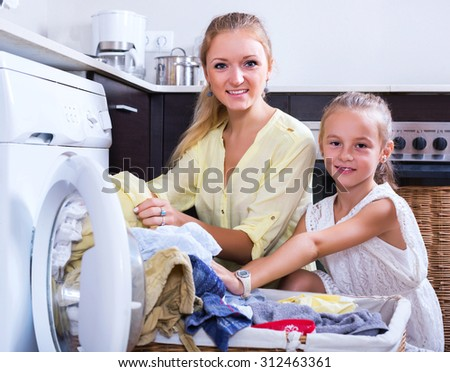 Smiling housewife and little girl doing laundry together at home - stock photo