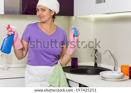 Smiling housewife holding up detergent and soap smiling playfully at the camera as she stands at the sink in her apron and cap - stock photo