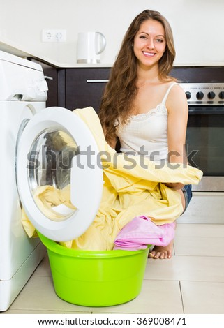 Smiling housewife using washing machine at home kitchen