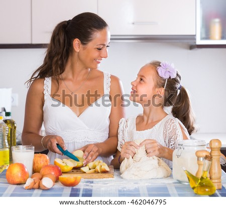 Smiling housewife with daughter preparing apple pie in kitchen