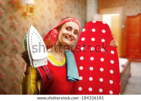 Smiling housewife with ironing-board and iron - stock photo
