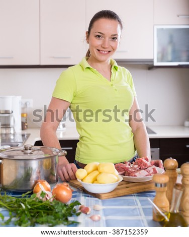 Smiling housewife with meat, potatoes and casserole at kitchen table