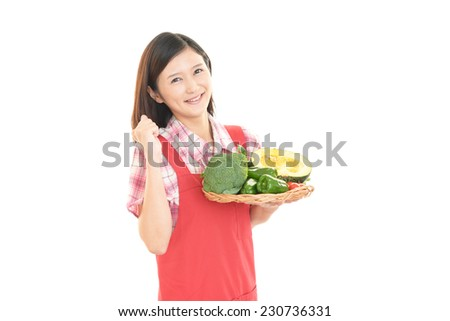 Smiling housewife with vegetable
