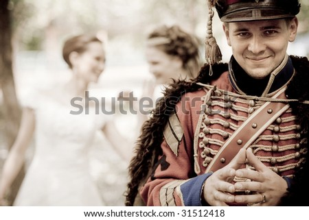 Smiling hussar in vintage outfit. Two pretty women on the background are discussing him. - stock photo