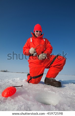 smiling ice fisherman fighting a big fish through the ice