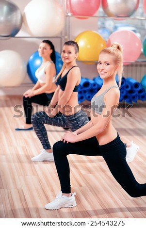 Smiling in satisfaction. Three beautiful young women in sports clothing exercising together while stretching in sports club  - stock photo