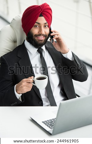 Smiling indian businessman is drinking coffee in his office and talking by phone. - stock photo