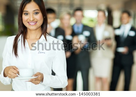 smiling indian businesswoman having coffee during conference break - stock photo