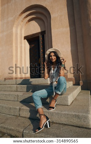 smiling indian lady in jeans, white shirt and white hat against ancient building. She is in harsh morning light. She is positive and playful. Building looks like church or eastern temple - stock photo