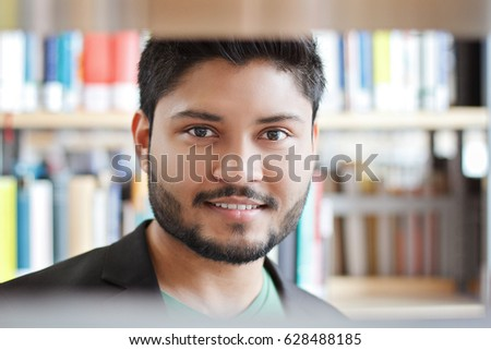 Smiling indian student at the library