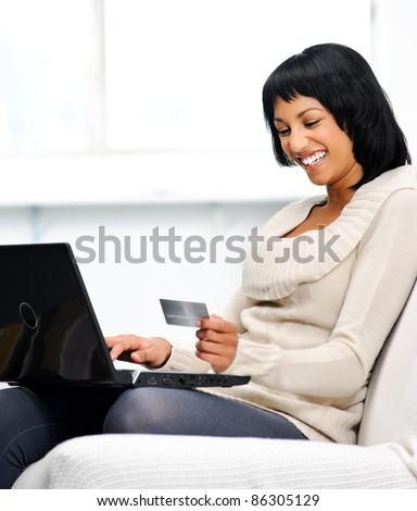 Smiling indian woman with laptop and credit card at home