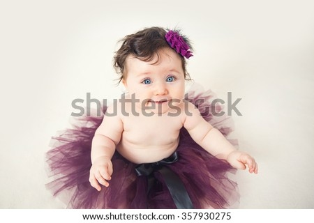 Smiling Infant child girl on blanket wearing a violet dress on a white background. - stock photo
