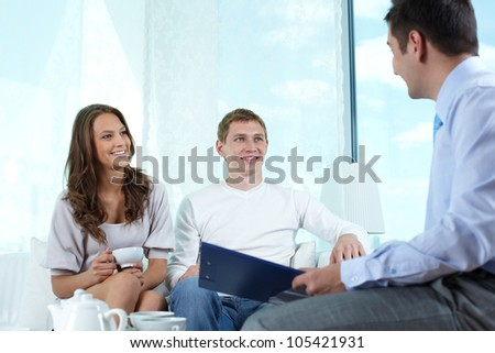 Smiling insurance agent making a business proposition to a lovely couple - stock photo