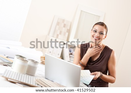 Smiling interior designer with color swatch and paint at office - stock photo