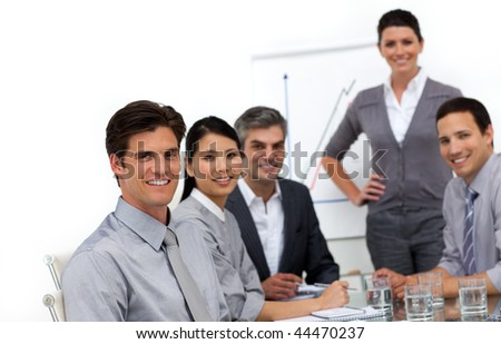 Smiling international business people at a presentation looking at the camera
